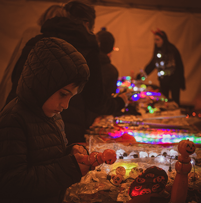 A child looking at Nights of the Jack souvenirs